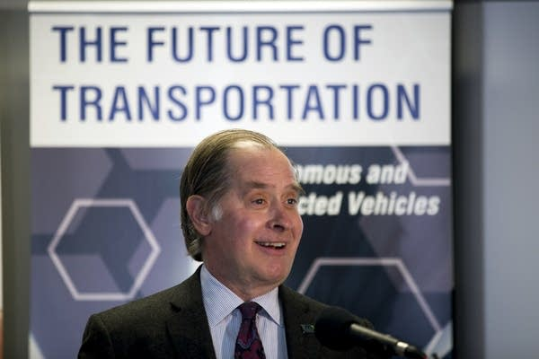 """A man speaks, standing in front of a banner saying """"The future of transportation."""""""