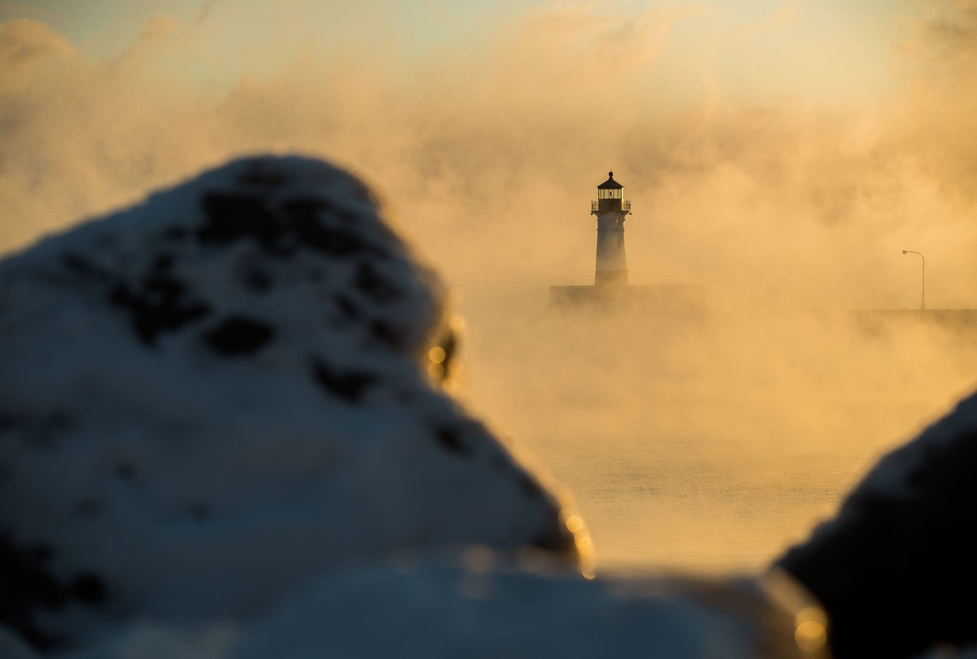 Sunlight shrouds and sea smoke rises over the North Pier Light in Duluth.