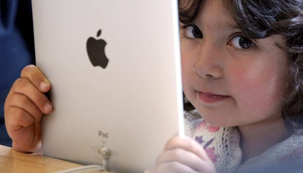 Young girl holds iPad