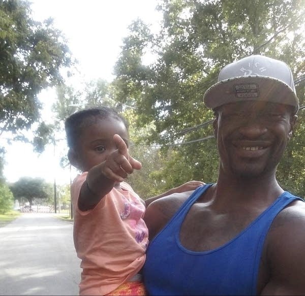 A man smiling at the camera holding a young child.