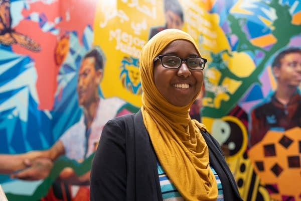 A woman stands for a portrait in front of a colorful mural.