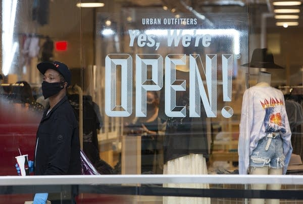"A person wearing a face mask walks past a sign reads ""Yes, we're open."""