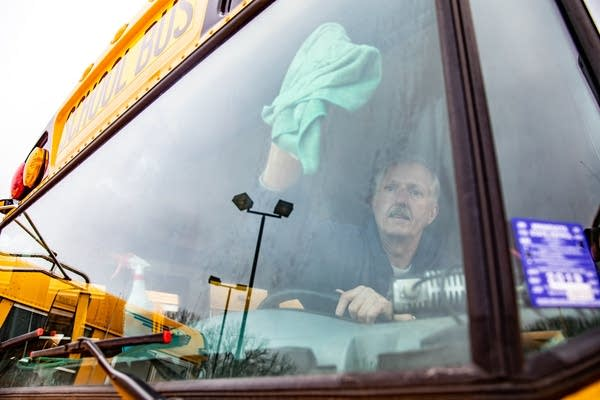 A man wipes the inside of a windshield.