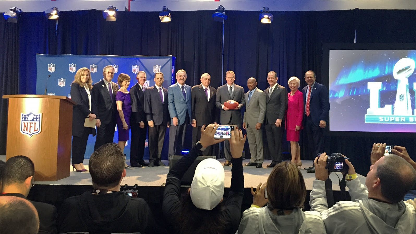Roger Goodell hands the game ball to the Minn. Super Bowl Host Committee.