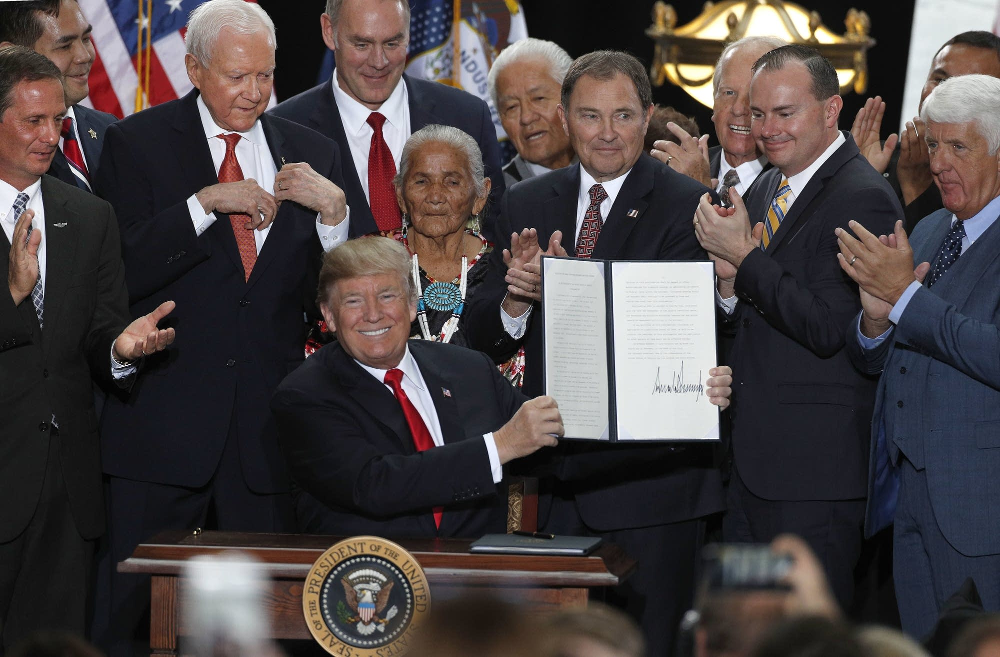 Trump shows an executive order he signed reducing national monuments.