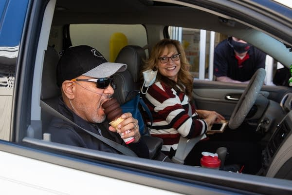 A man eats an ice cream cone with his wife in the drivers seat.