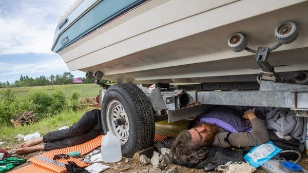 Two activists lay near a boat on a trailer in the road.