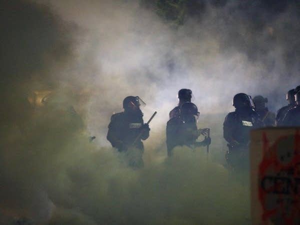 Police in riot gear are seen through clouds of tear gas
