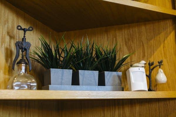 An Assured Living sensor sits on a shelf.