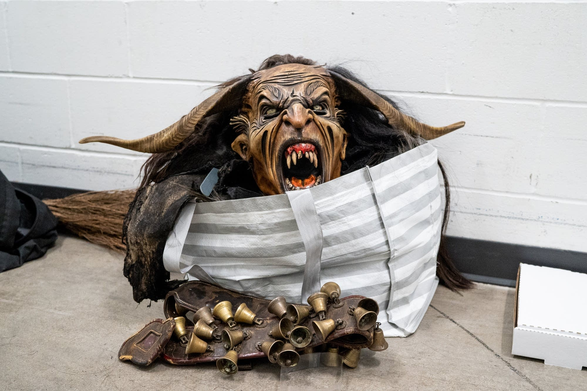 A Krampus mask and bells sit in a hallway.