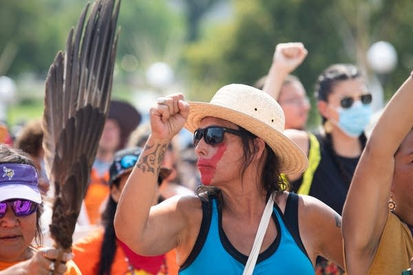 A woman walks with her fist in the air.
