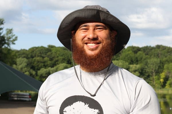 A man with a beard wears a hat and smiles.