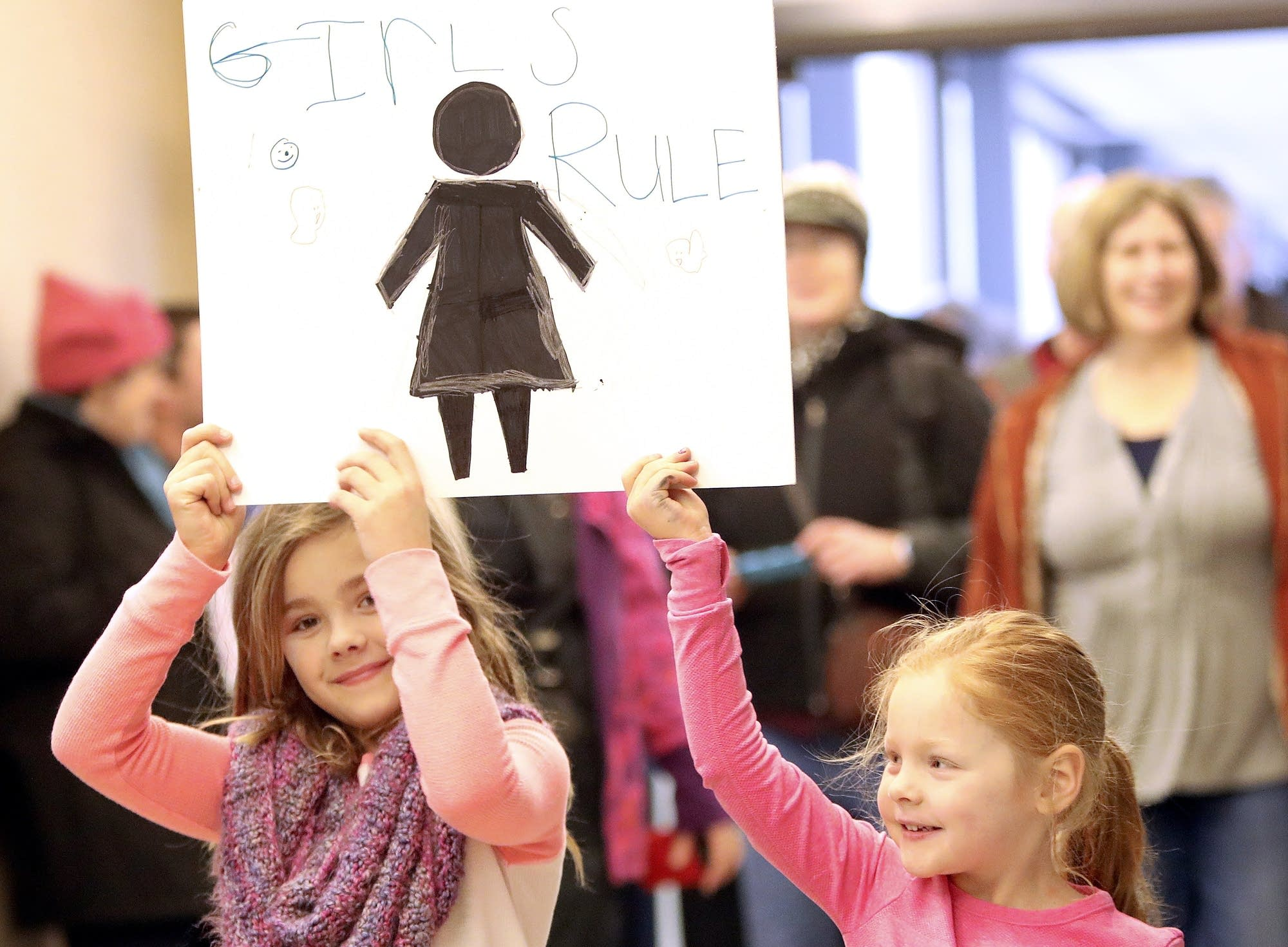 Iris Hutchinson and Lily Griffith carry a handmade sign.