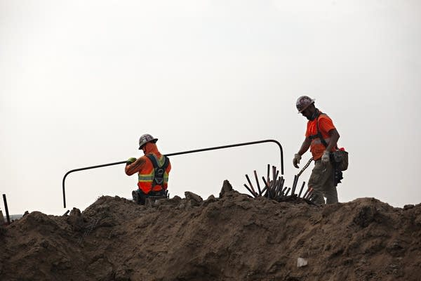 Two construction workers move materials on a construction site.