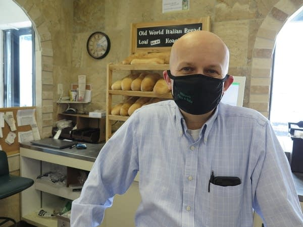 A man in a mask smiles inside a deli.