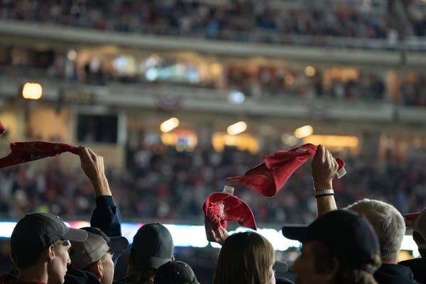 People swing red hankies above their heads.
