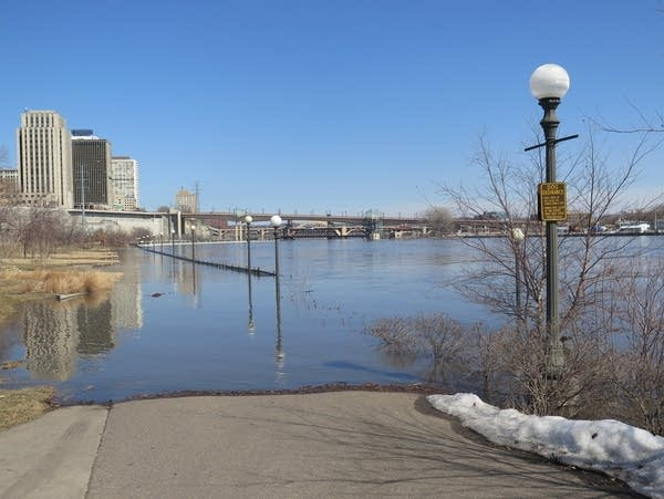A flooded walkway along the banks of the Mississippi River in St. Paul.