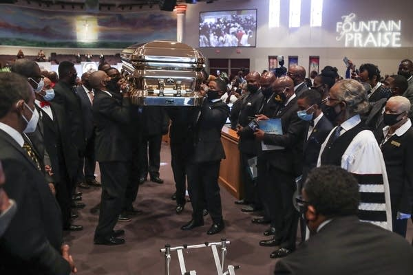 Pallbearers recess out of the church with the casket.