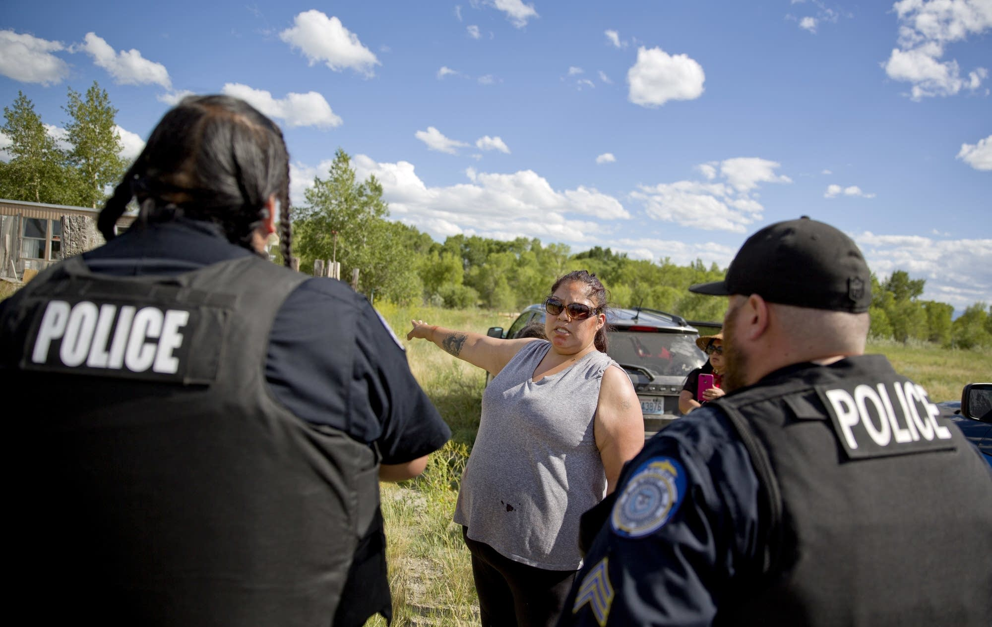 Lissa Loring points Blackfeet law enforcement officers to a trailer.