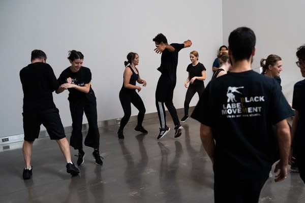 People in black clothing jump around and dance on a white wall.