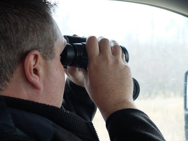 a man sitting in a truck looks through binoculars