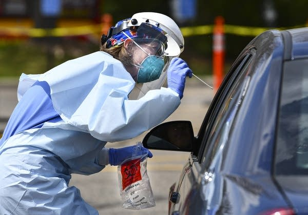 A person wearing personal protective equipment stands at a car window