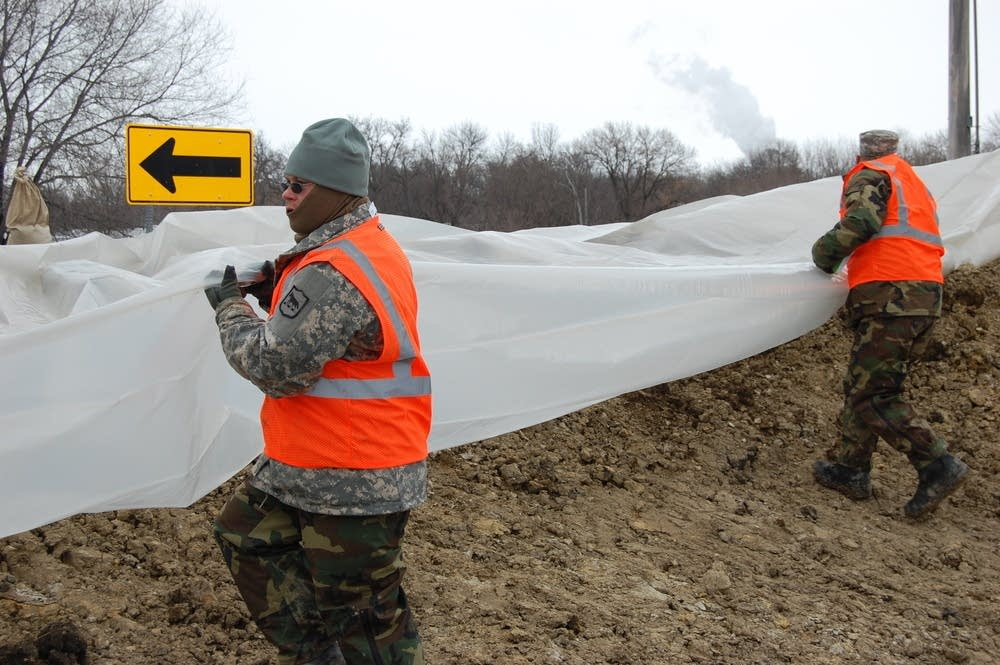 National Guard troops cover the dike in plastic
