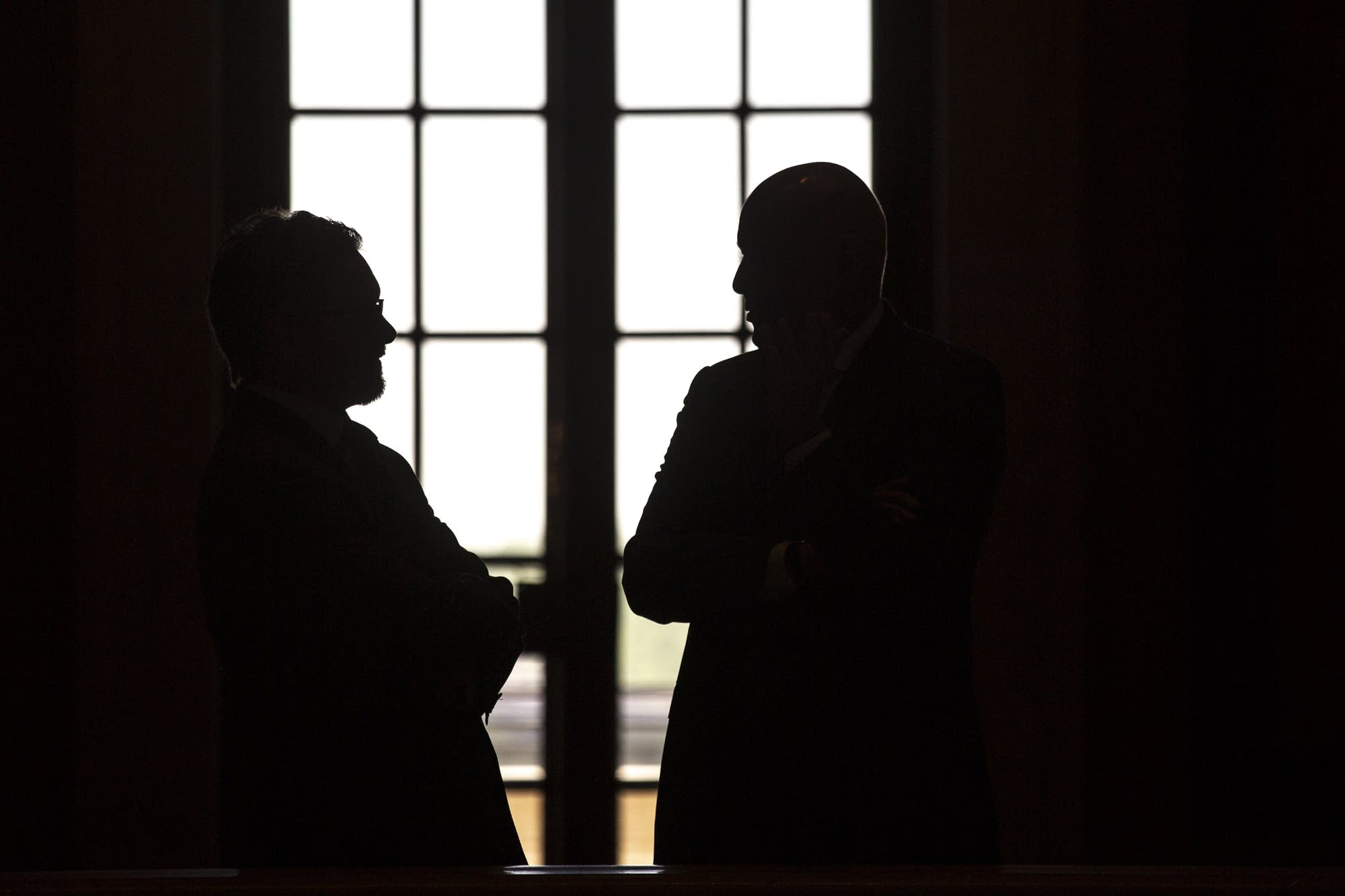 Two men talk on the second floor of the Minnesota State Capitol.