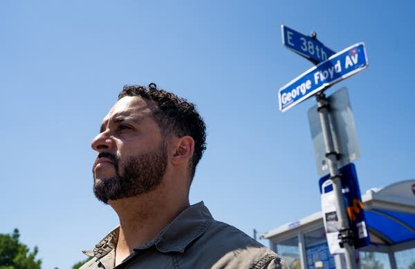 A man stands in front of a street sign.