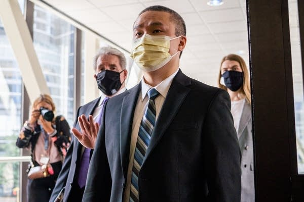 Group of people wearing face masks walk into a building.