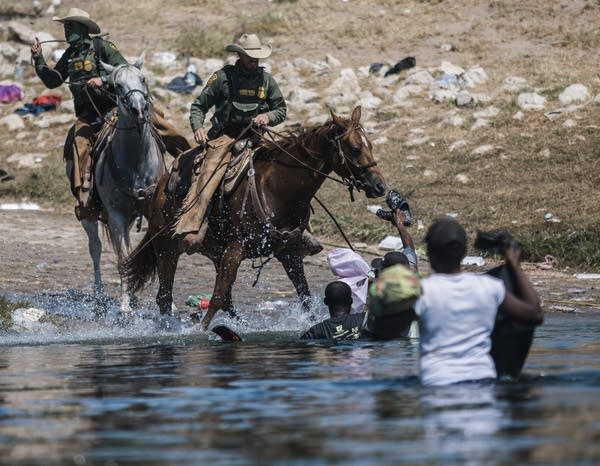 Customs and Border Protection officers on horses confront migrants.