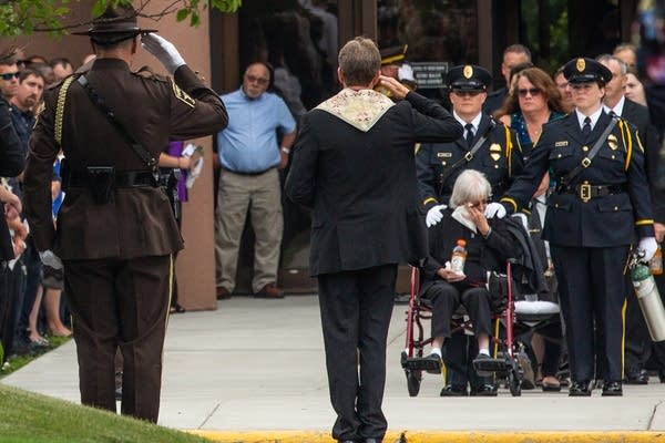 Law enforcement officers salute mourners of Officer Joseph Gomm.