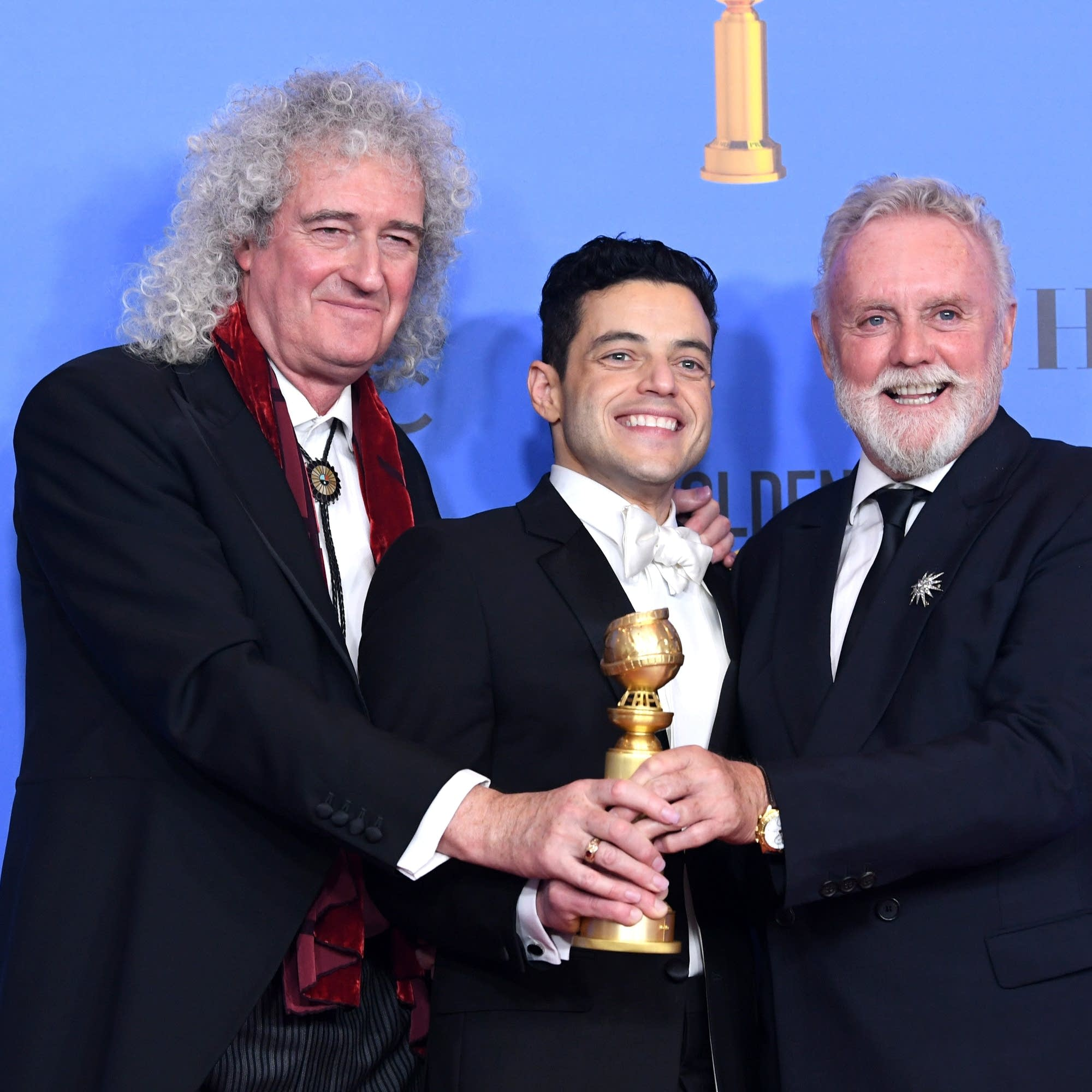 Brian May and Roger Taylor of Queen pose with Rami Malek.