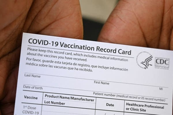 A COVID-19 vaccination card in someone's hands.