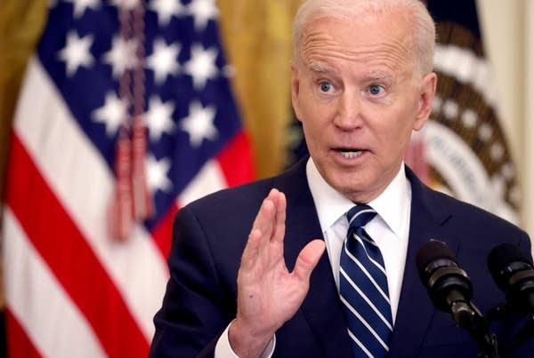 A man speaks behind a podium.