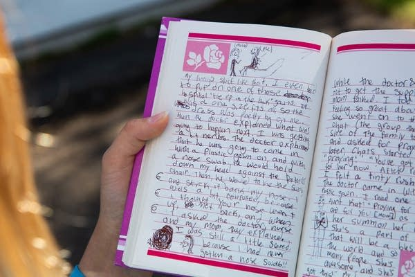 A child's handwriting fills a notebook.