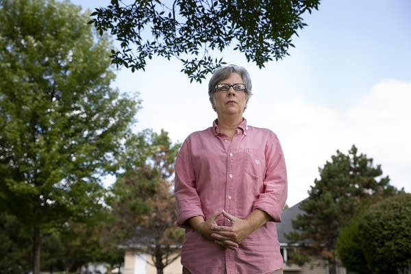 A woman wears a pink shirt and stands outside.