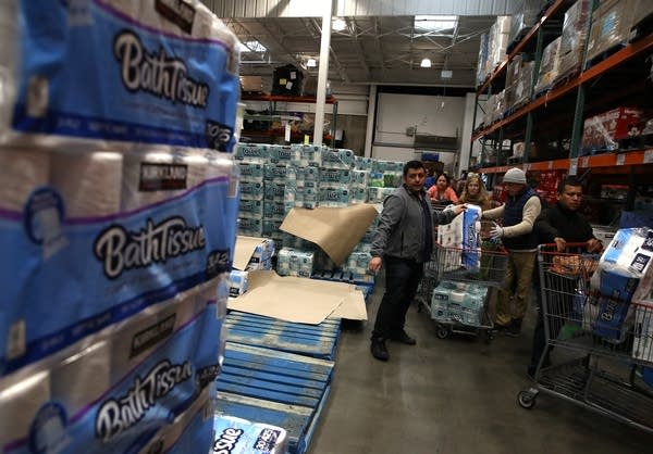 A Costco employee hands out packages of toilet paper.