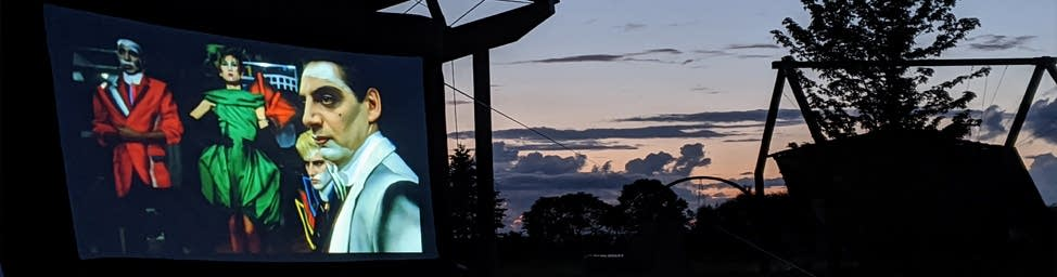 Wide photo of image projected on screen in front of sunset.