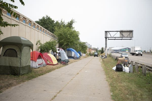 Tents line the sidewalk next to Hiawatha Ave. in a homeless encampment.
