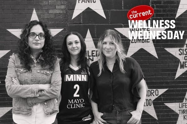 Three women standing against First Avenue star wall.