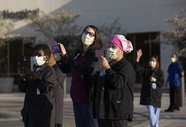 People wearing face masks and scrubs wave and hold phones.