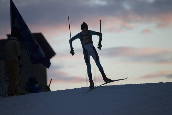 A high school nordic skier heads over the top of the Birkebeiner bridge.