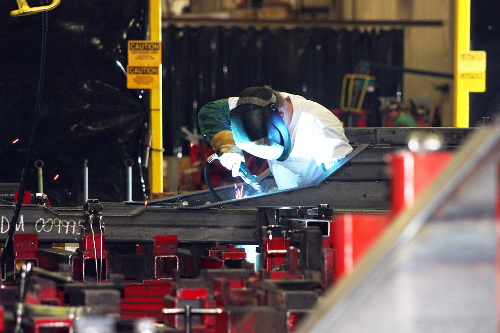 A welder works on a bus at New Flyer