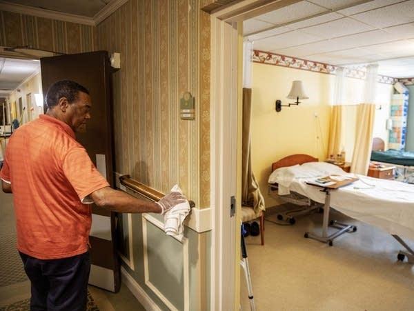 Guilherme Gomes sanitizes a hand rail