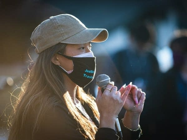 A woman wearing a mask speaks into a microphone