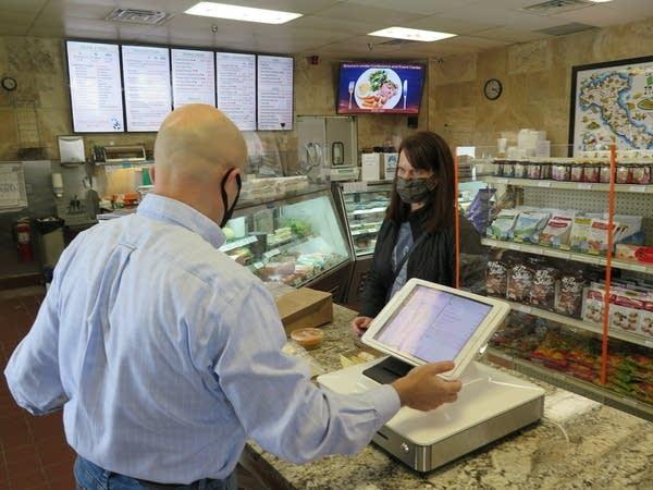 A man behind a cash register talks to a customer.