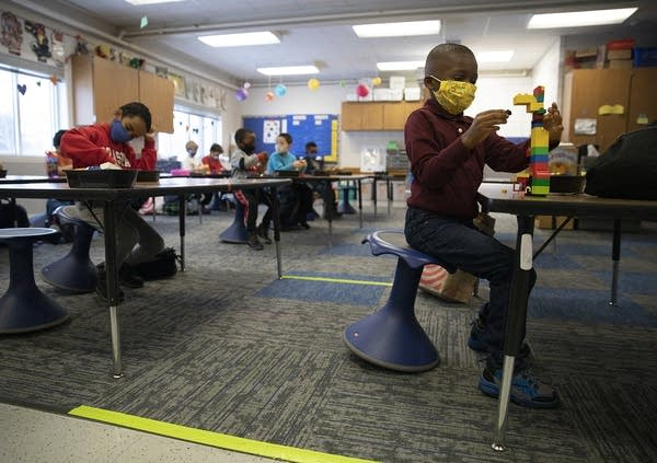 Kids wearing face masks sit at tables in a classroom.