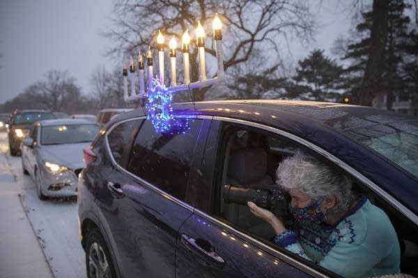 A woman takes photographs from inside a car with a menorah on its roof.