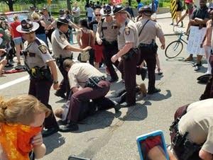 Minnesota State Patrol troopers detain demonstrators.